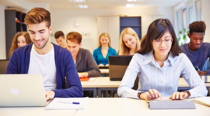 סטודנטים יושבים בשיעור עם טאבלטים ומחשבים