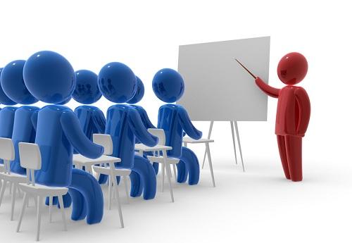 מורה עומד ומציג ללדי בכיתה, מול לוח