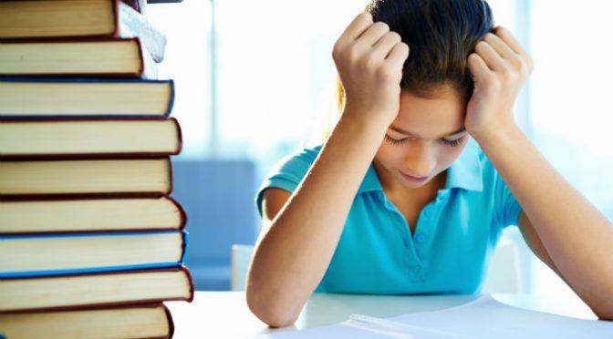 ילד יושב ומחזיק את ראשו בגלל קשיים בלמידה לידו ספרים