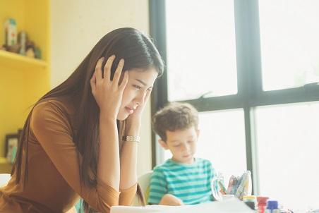 אשה עם ידים על האזניים נראית מודאגת. לידה יושב ילד ומצייר.