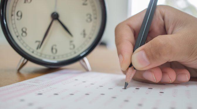 יד מחזיקה בעפרון וכותבת מבחן בצד שעון