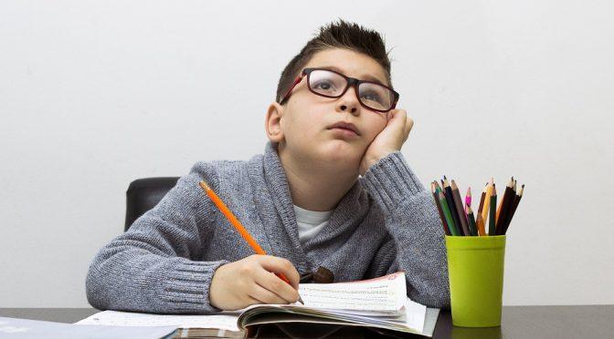 ילד בוהה באויר עם עפרון ביד